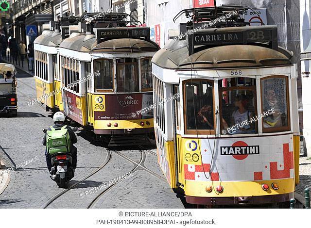 12 April 2019, Portugal, Lissabon: Tram number 28 goes through Praca Luis de Comoes. The central square in the centre of Lisbon connects the districts of Bairro...