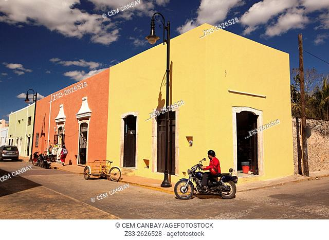 Street scene from the town center with a man driving a motorbike in the foreground, Valladolid, Yucatan Province, Mexico, Central America