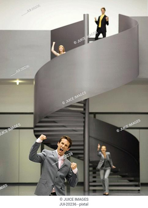 Businesspeople celebrating on spiral staircase