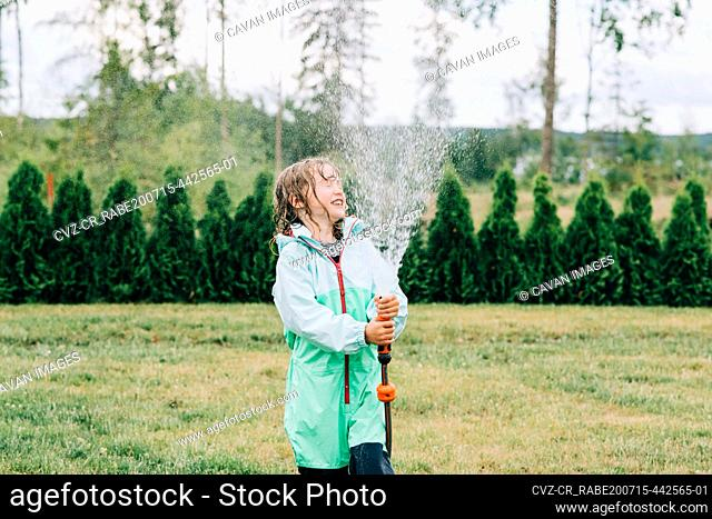 girl spraying water in her face with a hose in the yard in summer