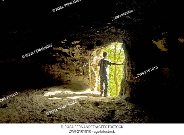 Traveler looking the landscape at the entrance of the Gobas de Laños cave, province of Palencia, Castilla y Leon, Spain