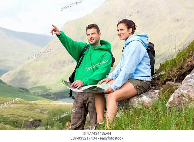 Couple resting after hiking uphill and consulting map in the countryside