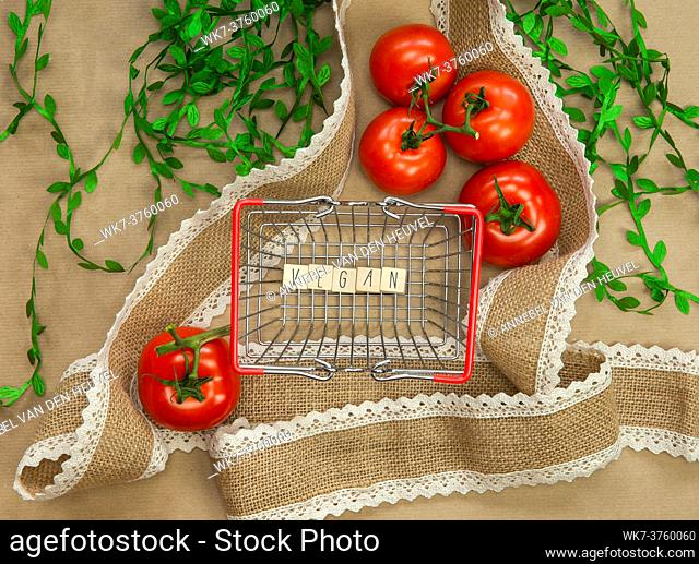 Vegan written on wooden cubes surrounded with vegetables in shoppin basket top view with craft paper background, Vegan, Healthy food, Vegetarian concept