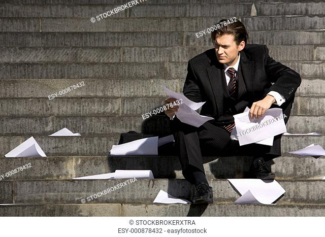 Unhappy businessman suffering from world financial crisis while sitting on stairs