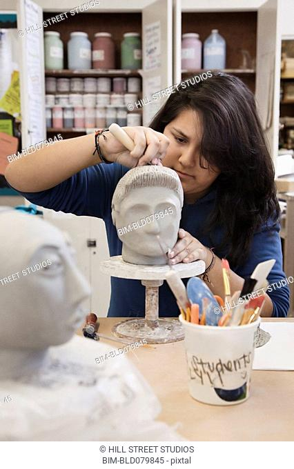 Hispanic student sculpting bust in classroom