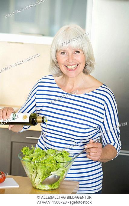 Elderly woman preparing salad with olive oil