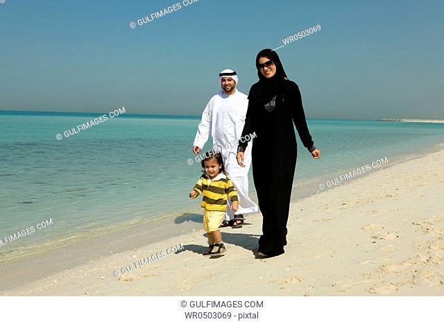 Arab family walking at the beach