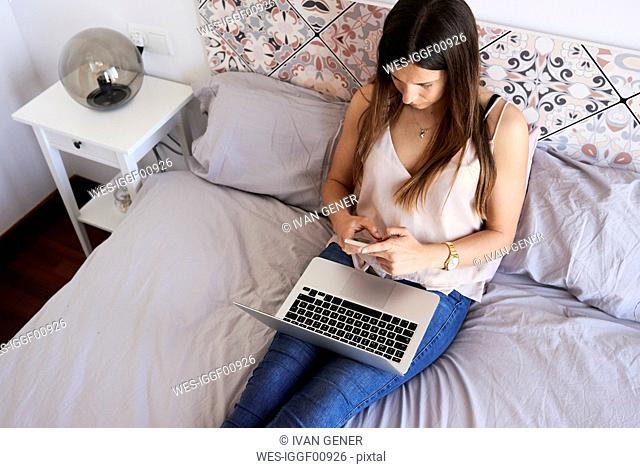 Young woman sitting on bed with laptop using smartphone