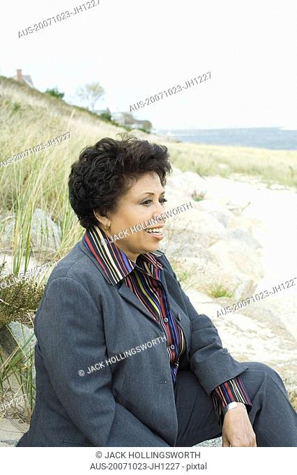 Mature woman sitting on the beach and smiling