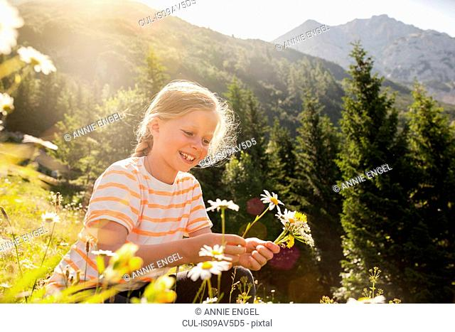 Young girl in field, picking flowers