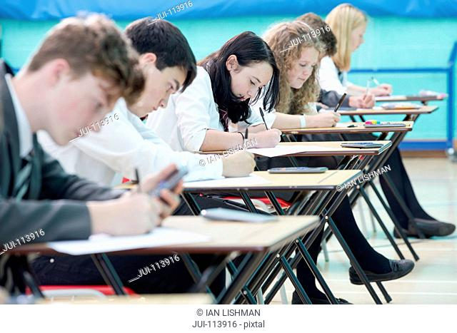 Focused middle school students with calculator taking examination at desks