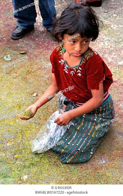 Sad Mayan child with confetti in the middle of a Maya procession in Santiago de Atitlan, Guatemala, Atitlansee, Santiago de Atitlan