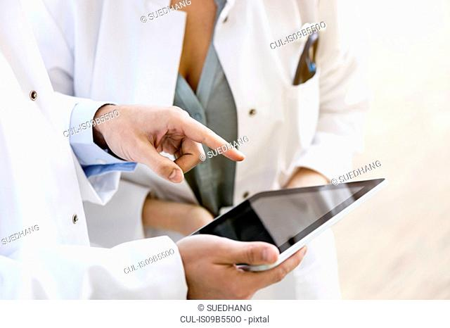 Two doctors looking at digital tablet, mid section, close-up