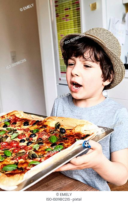 Young boy holding freshly baked pizza