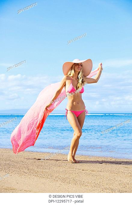 Beautiful Woman Walking On Tropical Beach With Sarong Blowing In The Wind