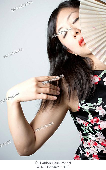 Portrait of Asian woman with closed eyes holding fan in front of grey background