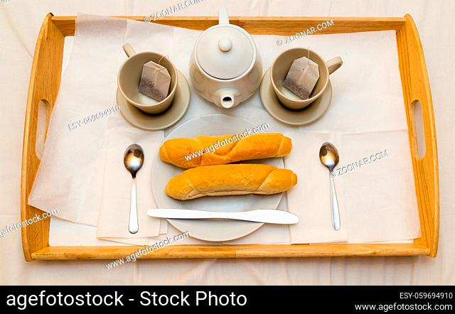 Covered breakfast for two on a wooden tray are two cups teapot baguettes on fresh crispy plates