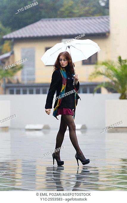 Teenager girl street-walking on rainy day