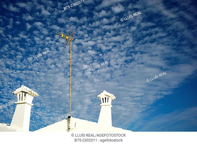 Two chimneys in the roof of a house and a television antenna of a Mediterranean house with clouds and blue sky in the background