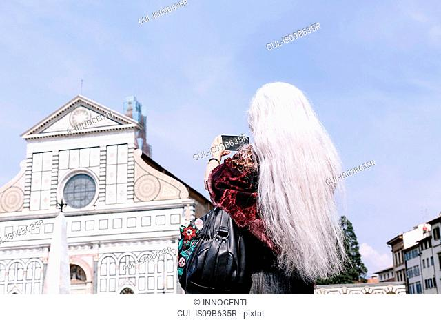 Long grey haired woman photographing Santa Maria Novella church, Florence, Italy