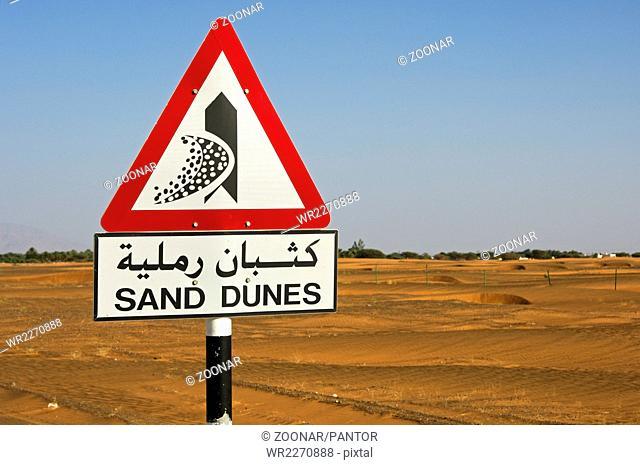 Road sign warning of shifting sand dunes, Oman