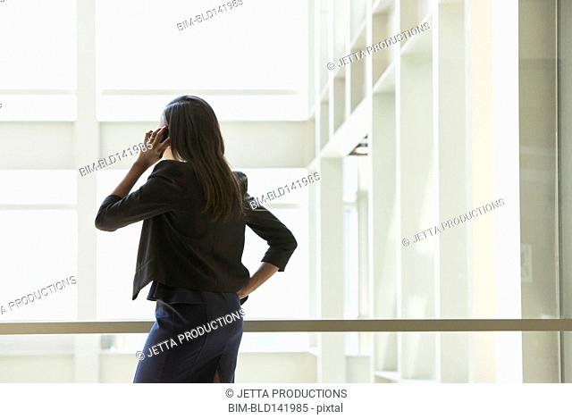 African American businesswoman talking on cell phone in office