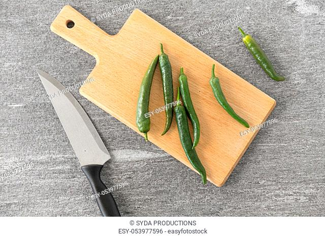 green chili peppers and knife on cutting board