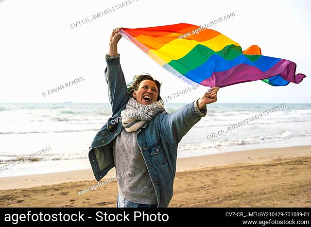 Woman running with colorful LGBT flag waving on the beach