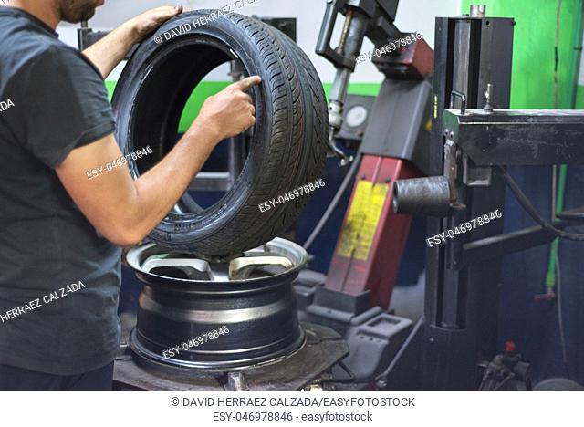 Professional mechanic using machine for tyre change