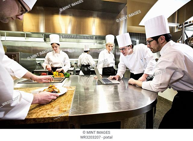 A crew of chef's working in a commercial kitchen, while several chefs wok on a laptop computer