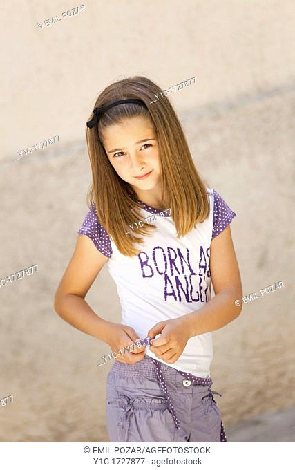 Young girl is adjusting a hem of her t-shirt
