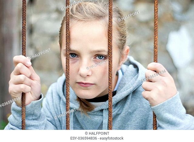 Sad lonely child is behind grid