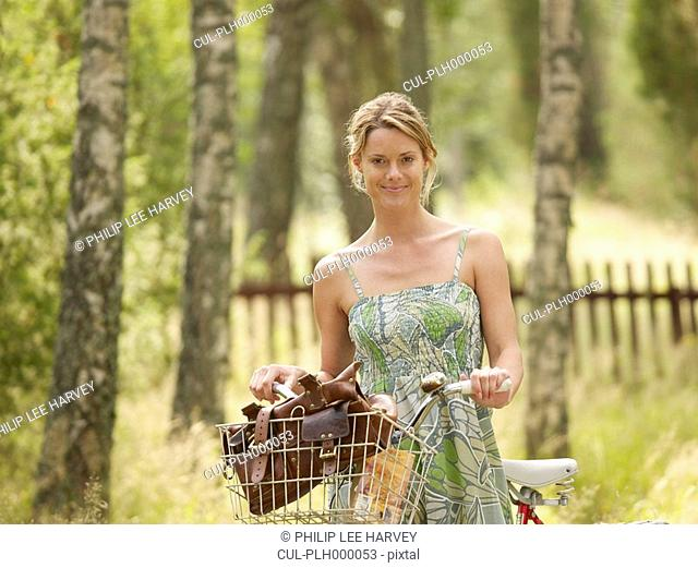 Woman standing with bike by wooden fence