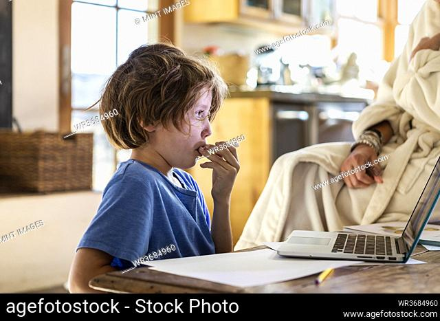 young boy at home having his temperature taken with a thermometer