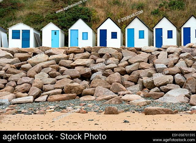 colorful row of small wooden beach cottages on the rocky Normandy coast in Barneville-Carteret