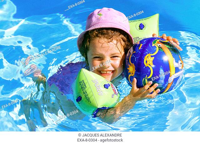 Young girl smiling with ball in swimming pool