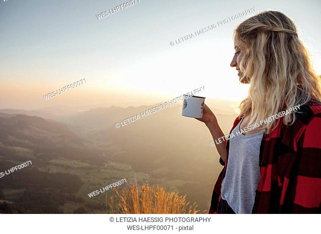 Switzerland, Grosser Mythen, young woman on a hiking trip at sunrise holding a cup