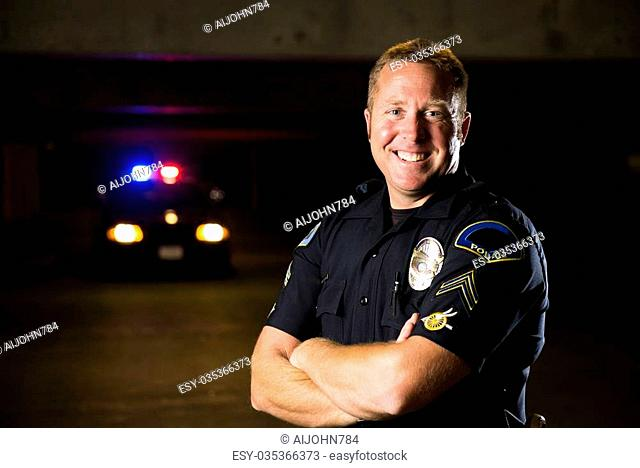 A smiling police officer with his patrol car in the background