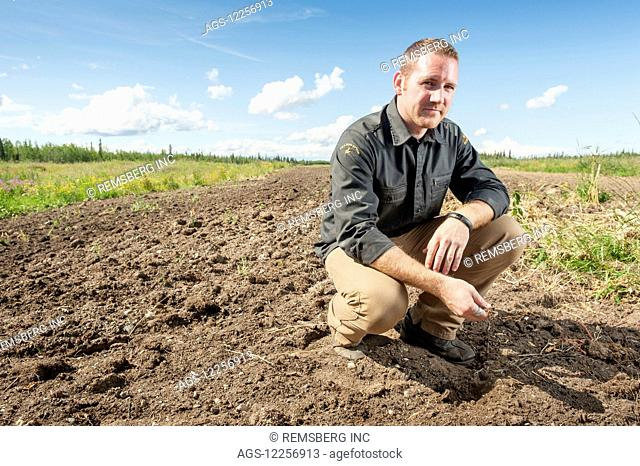 Portrait of barley farmer kneeling over tilled field; Delta Junction, Alaska, United States of America