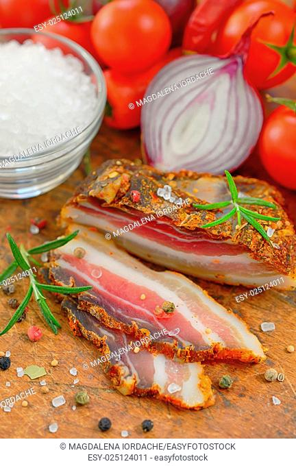 Traditional bacon with vegetables on wooden table