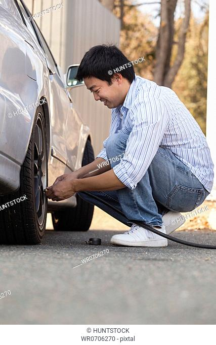 Chinese man putting air in his car tires