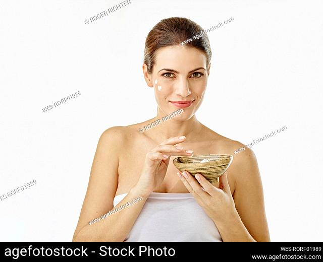 Portrait of smiling woman with bowl of moisturizer against white background