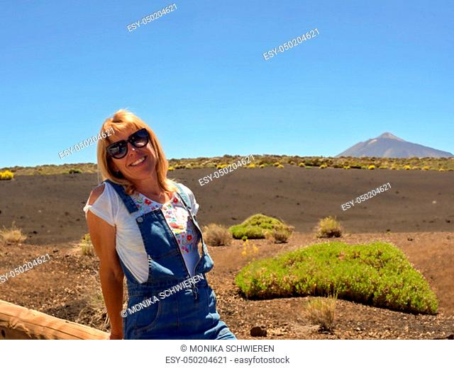 A woman sitting on a trunk, wearing sunglasses, white shirt, blue short dungarees, has blonde long hair, in the background a magnificent volcanic landscape with...