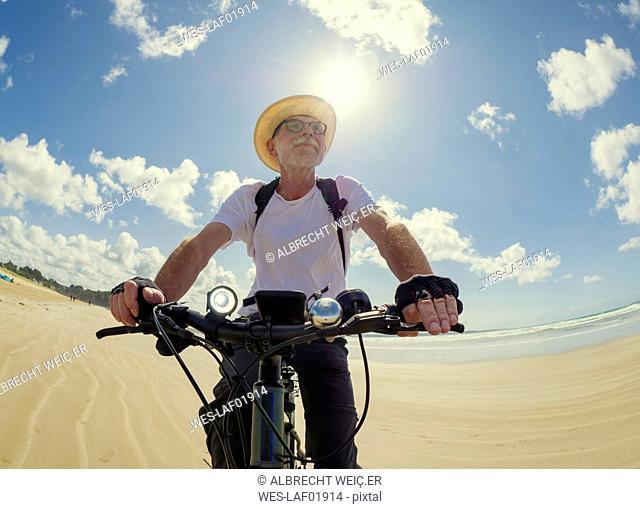 France, Bretagne, Sainte-Anne la Palud, Plage de Treguer, senior man riding mountain e-bike on beach