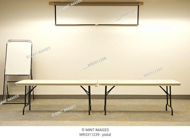 Empty tables under projector screen in classroom