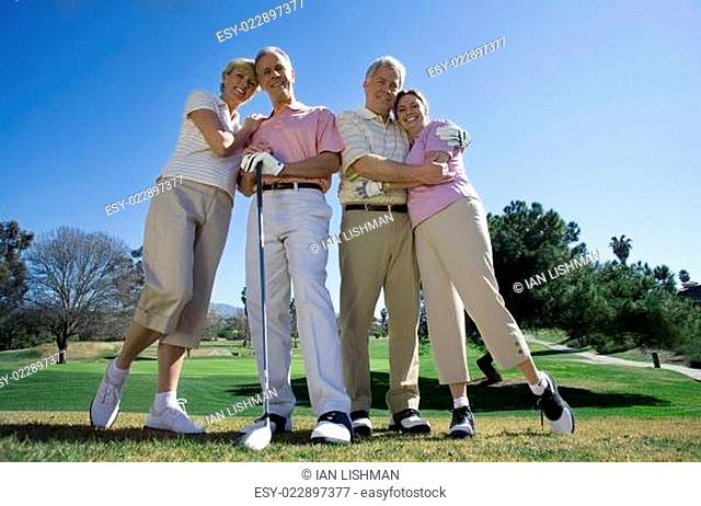 Two mature couples standing side by side on golf course, embracing, smiling, front view, portrait (surface level)