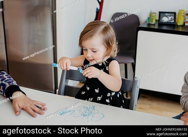 Girl sitting at table and holding pen
