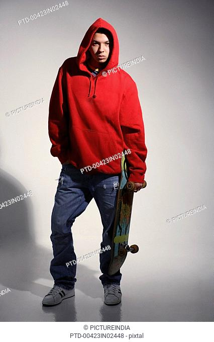 young man wearing red hooded sweatshirt holding skateboard