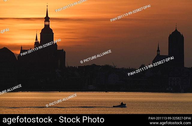 13 November 2020, Mecklenburg-Western Pomerania, Stralsund: Orange at sunset is the sky above the Hanseatic City of Stralsund with the Marienkirche (l) and the...