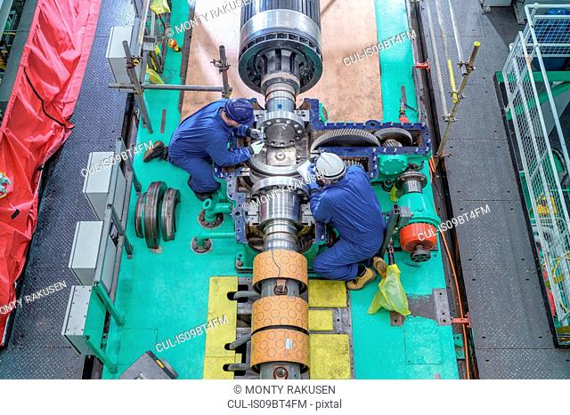Overhead view of engineers inspecting gears on generator in turbine hall of nuclear power station during outage